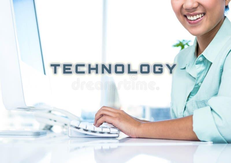 Bebouwd beeld van glimlachende onderneemster die aan computer met technologietekst op kantoor werken stock foto's
