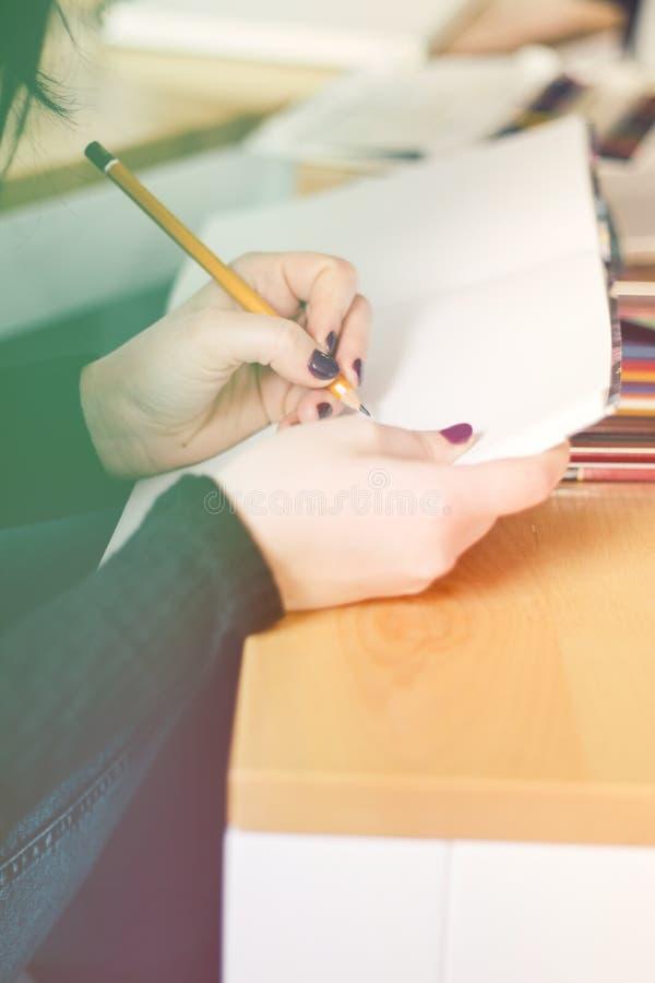 Bebouwd beeld van hand die van jonge vrouw nota's, het lichte stemmen nemen royalty-vrije stock afbeelding