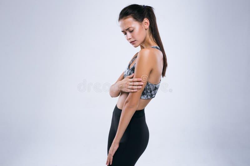 Bebouwd beeld van jonge geschiktheidsvrouw die wapenpijn hebben terwijl status over grijze achtergrond stock fotografie