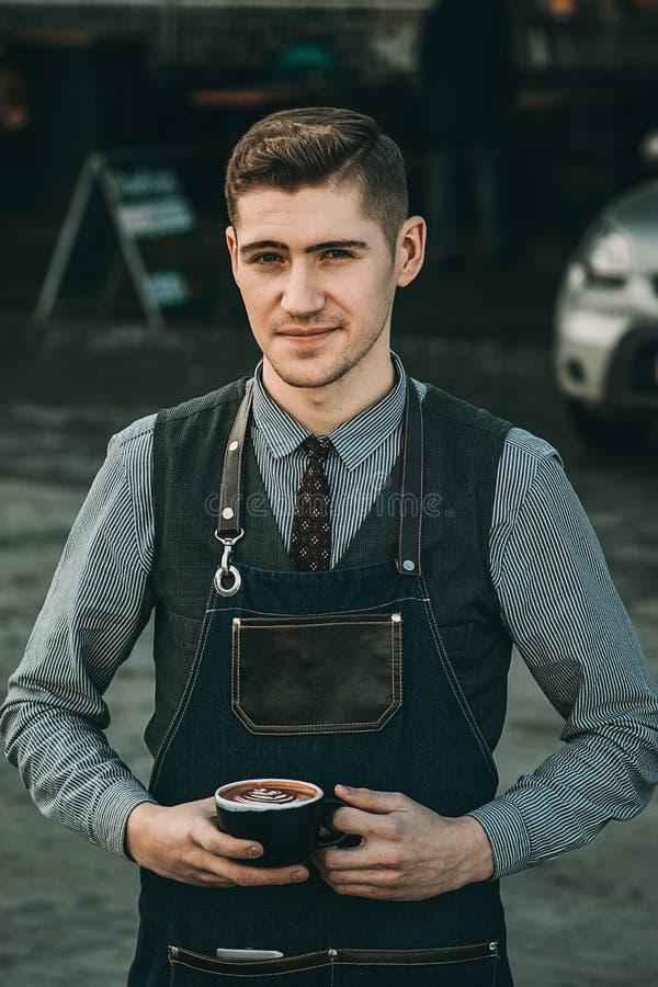 Bebouwd beeld van knappe barista in een kop van koffie houden en schort die terwijl het werken bij de barteller in koffie glimlac royalty-vrije stock afbeelding