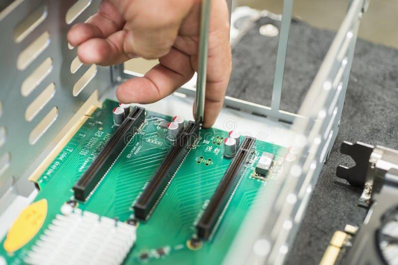 Bebouwd beeld van mannelijke technicus die PCI-groeven in computerfabriek herstellen stock afbeeldingen