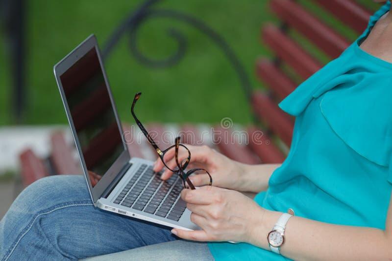 Bebouwd beeld van mooi meisje in de kleren die van Jean laptop met behulp van terwijl het zitten royalty-vrije stock fotografie