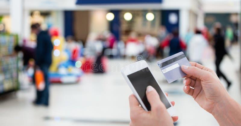 Bebouwd beeld van persoon die slimme telefoon voor het betalen van rekening door debetkaart met behulp van stock afbeelding