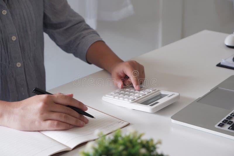 Bebouwd beeld van professionele onderneemster die op haar kantoor via laptop jonge vrouwelijke manager werken die draagbaar compu royalty-vrije stock afbeeldingen