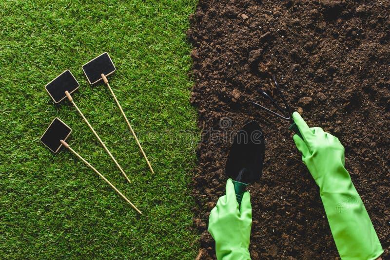 bebouwd beeld van tuinman in beschermende handschoenen die met het tuinieren hulpmiddelen en lege borden aan gras werken stock foto