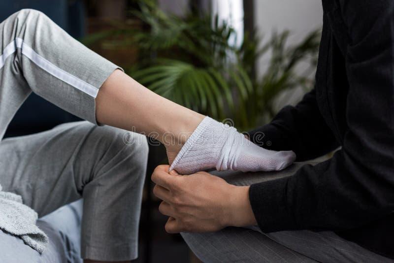 bebouwd beeld van vriend die sok op meisje dragen royalty-vrije stock afbeeldingen