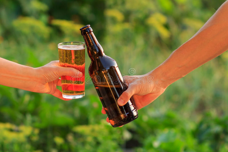 Bebouwd beeld van vrouw en de mens die glas van bier en fles klinken stock foto