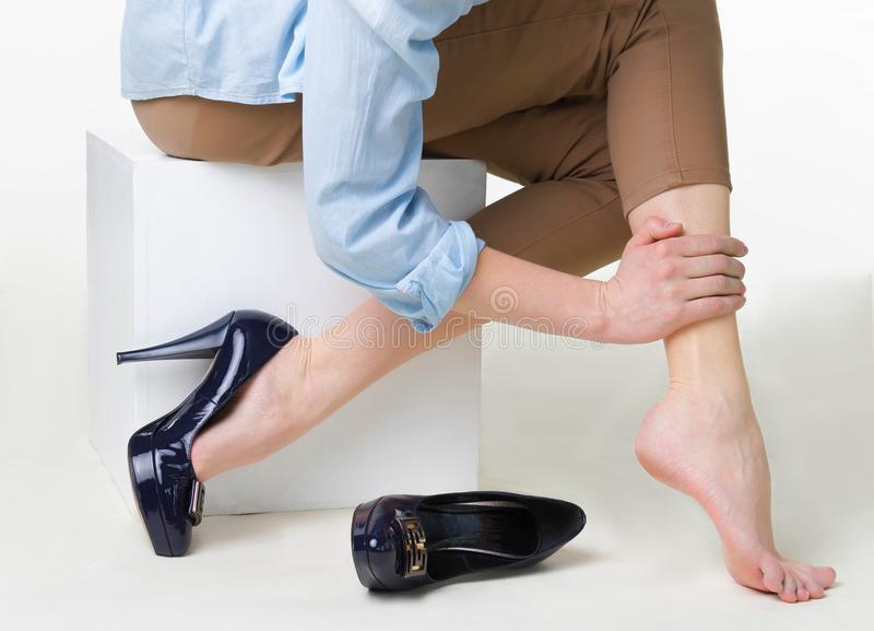 Bebouwd beeld van vrouw in hoge hielen die haar vermoeide benen masseren stock foto's