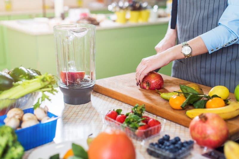 Bebouwd beeld van vrouwelijk kok scherp fruit aan boord van het voorbereidingen treffen smoothie in keuken stock fotografie