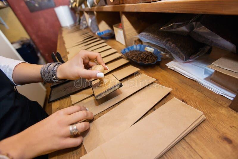 Bebouwd beeld van winkelbediende het stempelen document zakken bij koffieopslag royalty-vrije stock foto
