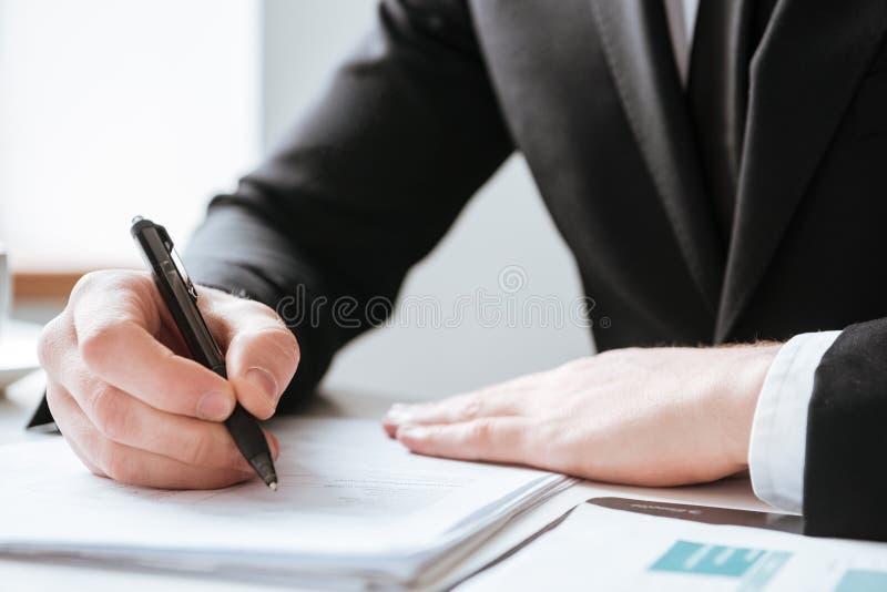 Bebouwd beeld van zakenman het schrijven nota's stock fotografie