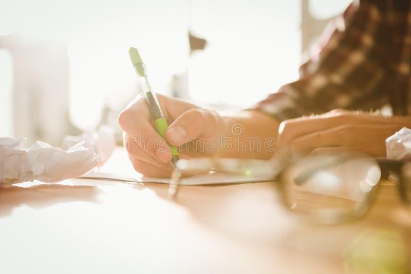 Bebouwd beeld van zakenman het schrijven op papier stock foto