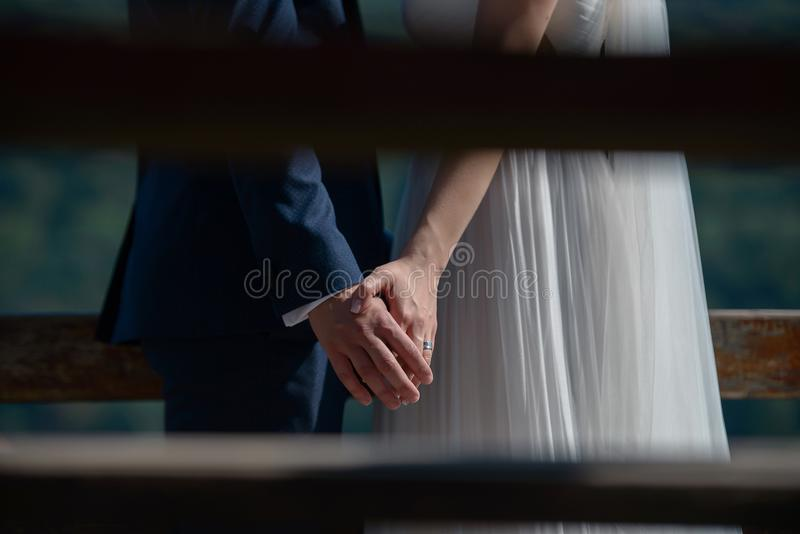 Bebouwd, paparazzi-stijl, privé schot van jonge Kaukasische bruid en de handen van de bruidegomholding royalty-vrije stock afbeelding