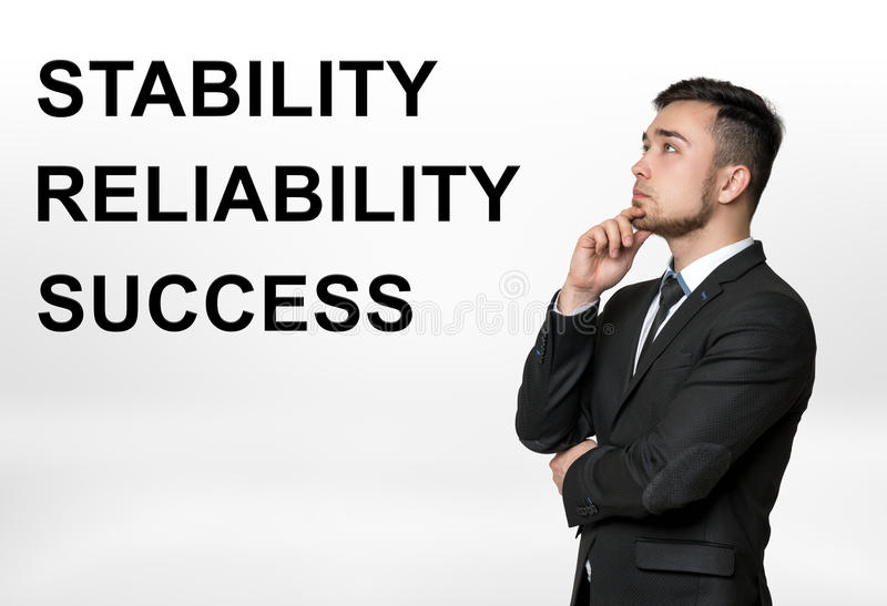Bebouwd portret van een zakenman denken met & x27 die; stabiliteit, betrouwbaarheid, success& x27; woorden naast hem stock afbeeldingen
