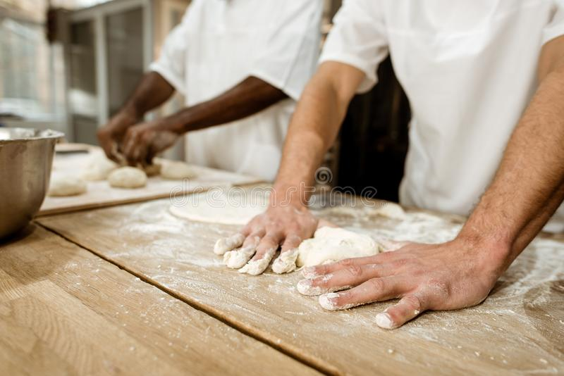 bebouwd schot van bakkers die deeg samen kneden stock fotografie
