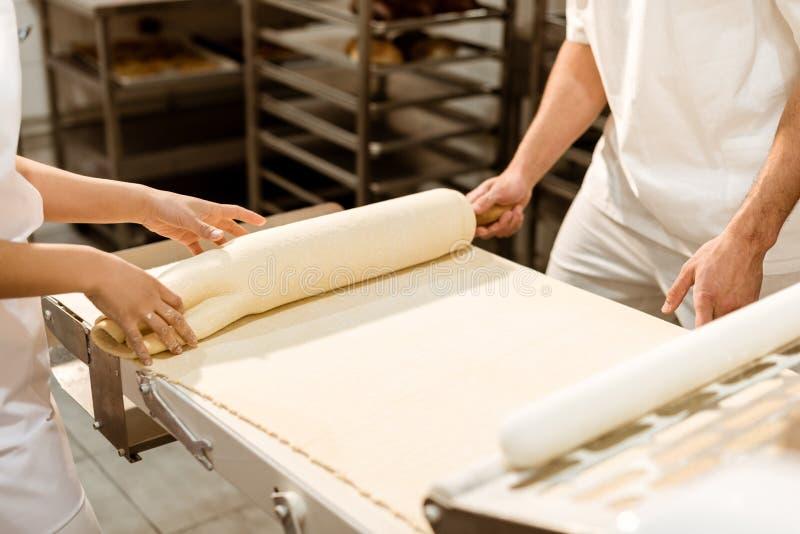 bebouwd schot van bakkers die met industriële deegrol werken stock foto