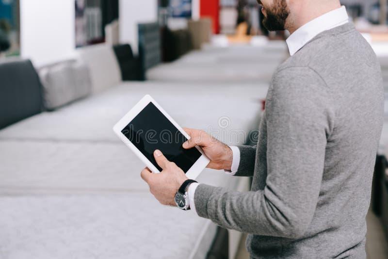 bebouwd schot van de mens die digitale tablet met het lege scherm in meubilairopslag gebruiken stock afbeeldingen