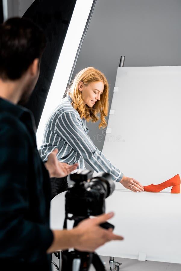 bebouwd schot van fotograaf die glimlachende vrouwelijke collega bekijken die schoen schikken stock fotografie