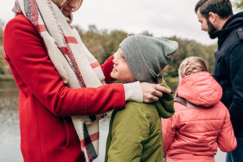 bebouwd schot van gelukkige jonge familie die met twee jonge geitjes tijd samen doorbrengen royalty-vrije stock fotografie