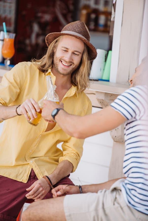 bebouwd schot van glimlachende jonge mannelijke vrienden die bierflessen clinking royalty-vrije stock afbeelding