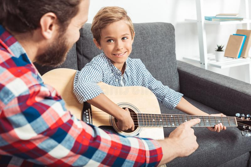 bebouwd schot van het vaderonderwijs die weinig zoon het spelen gitaar glimlachen stock afbeeldingen