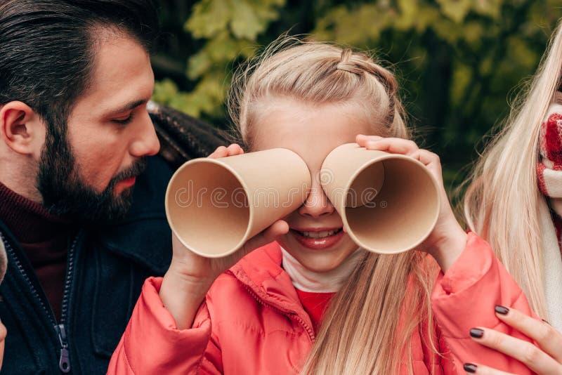 bebouwd schot van jonge ouders en leuk weinig dochter die pret met document koppen hebben stock foto's