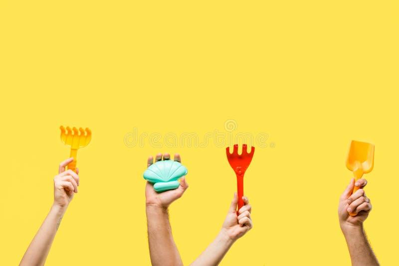 bebouwd schot van mannelijke en vrouwelijke handen die kleurrijk plastic speelgoed geïsoleerd houden stock afbeeldingen