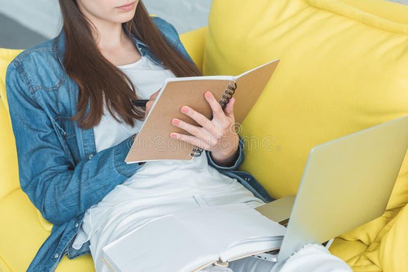 bebouwd schot van meisje het schrijven in notitieboekje en het gebruiken van laptop op bank stock afbeelding