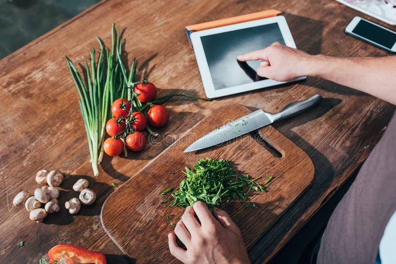 bebouwd schot van mens het koken met tablet stock afbeeldingen