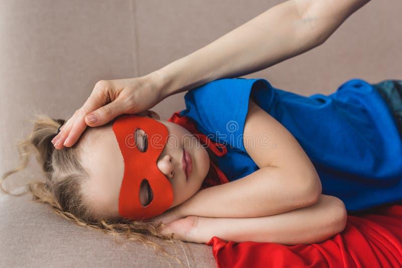 bebouwd schot van moeder wat betreft voorhoofd van weinig dochter in de slaap van het superherokostuum royalty-vrije stock afbeeldingen