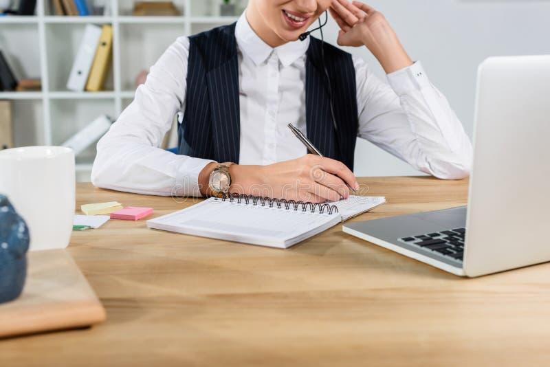 Bebouwd schot van onderneemsterzitting bij bureau, terwijl het spreken bij hoofdtelefoon en het schrijven stock afbeeldingen