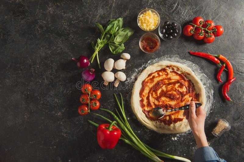 bebouwd schot van vrouw die saus op ruw deeg zetten terwijl het koken van Italiaanse pizza royalty-vrije stock afbeeldingen