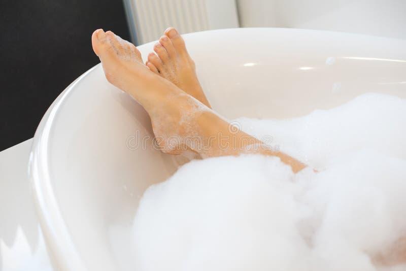 bebouwd schot van vrouwelijke benen in bad royalty-vrije stock afbeelding