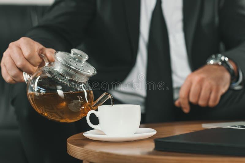 bebouwd schot van zakenman gietende thee stock afbeelding
