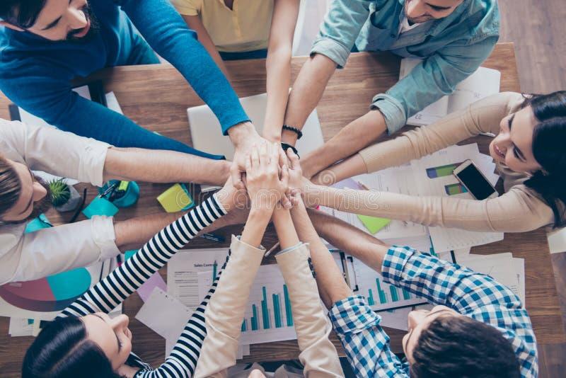 Bebouwd topview van zakenlui die hun handen zetten bovenop stock afbeeldingen