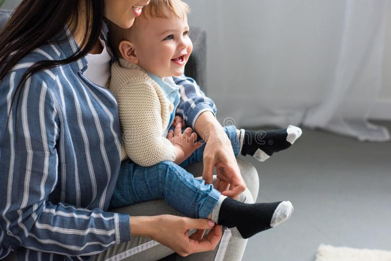 bebouwd vrolijk schot van moeder die weinig baby op bank kleden stock afbeeldingen