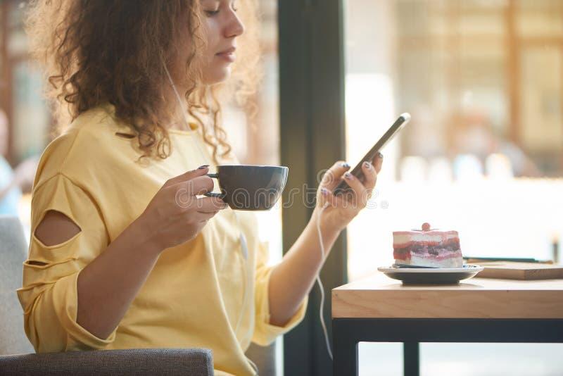 Bebouwd zijaanzicht die van meisje het drinken koffie, aan muziek in restaurant luisteren stock foto
