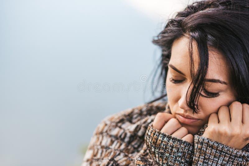 Bebouwde die close-up van dromerig mooi wijfje wordt geschoten die het comfortabele sweater stellen dragen tegen het meer Portret royalty-vrije stock fotografie