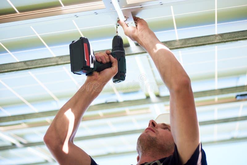 Bebouwde foto van arbeider die boor gebruiken door zonnepanelen op te zetten stock afbeelding