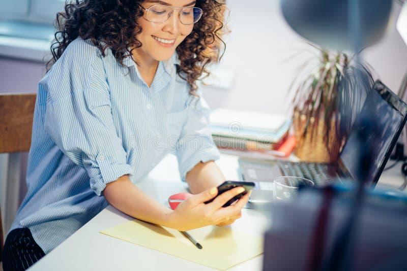 Bebouwde foto van jonge vrouw in toevallige clothers die zwarte cellphone binnen houden stock foto