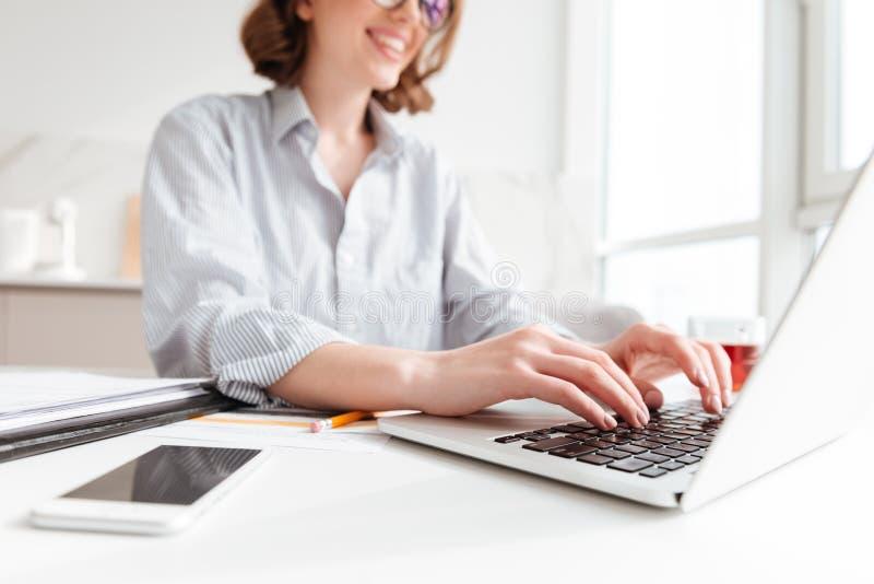 Bebouwde foto van vrij donkerbruine vrouw die e-mail op mede laptop typen stock foto