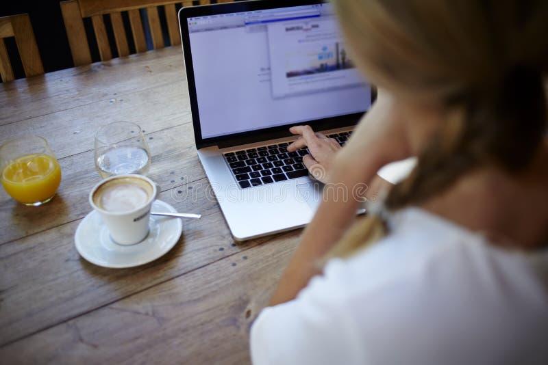 Bebouwde geschotene mening van jonge vrouw die aan laptop computer werken terwijl het zitten in het moderne binnenland van de kof stock afbeeldingen
