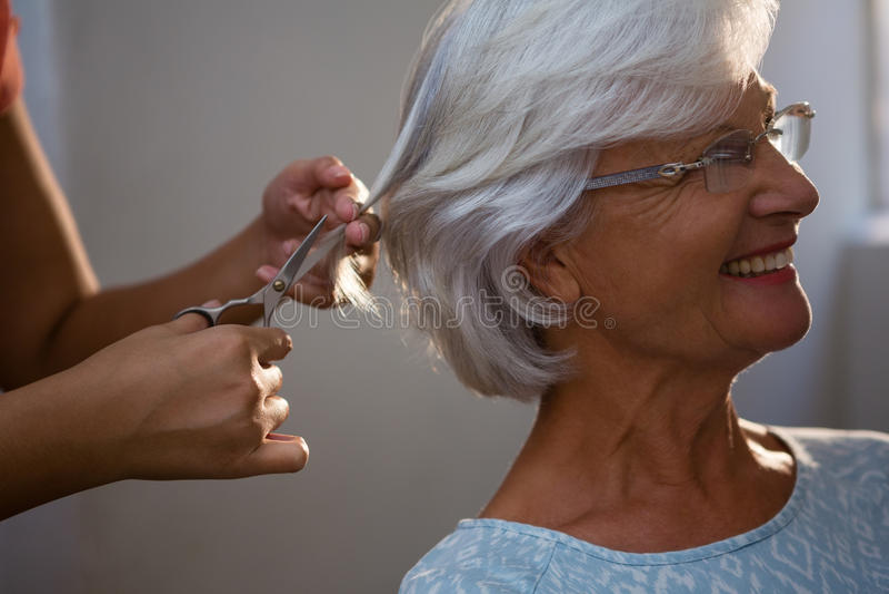 Bebouwde handen van hairsylist scherp haar van hogere vrouw royalty-vrije stock foto