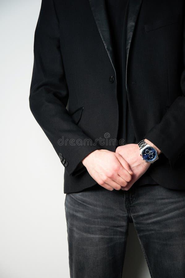 Bebouwde hoofdmens die in zwarte blazer zijn handen op de voorzijde met roestvrij staalhorloge houden op zijn rechts stock foto