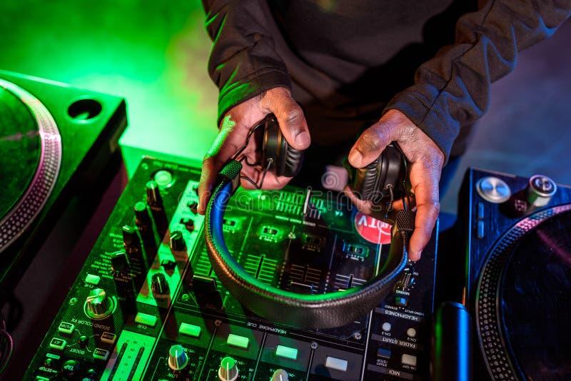 bebouwde mening die van de handen van DJ hoofdtelefoons over geluid houden royalty-vrije stock afbeelding