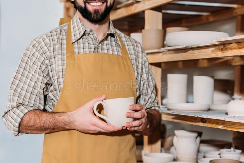 bebouwde mening die van mannelijke pottenbakker ceramische kop houden en zich dichtbij planken bevinden royalty-vrije stock afbeelding