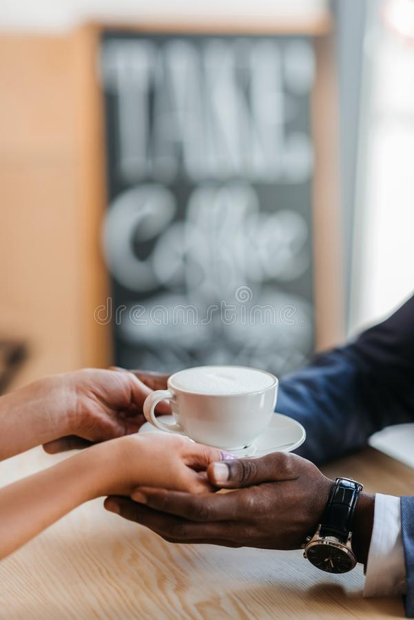bebouwde mening die van serveerster kop van koffie geven aan Afrikaanse Amerikaanse zakenman in koffie royalty-vrije stock afbeeldingen
