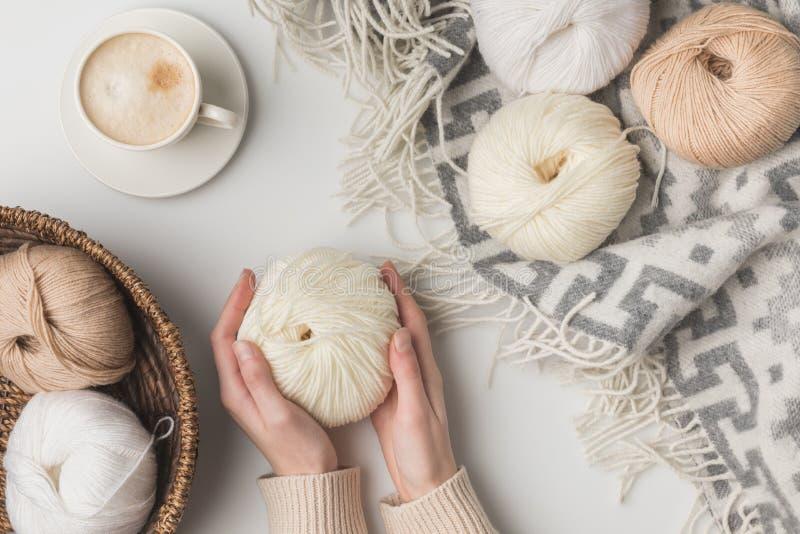 Bebouwde mening van de kop van de vrouwenholding koffie en garenballen op blaket en in mand stock foto's