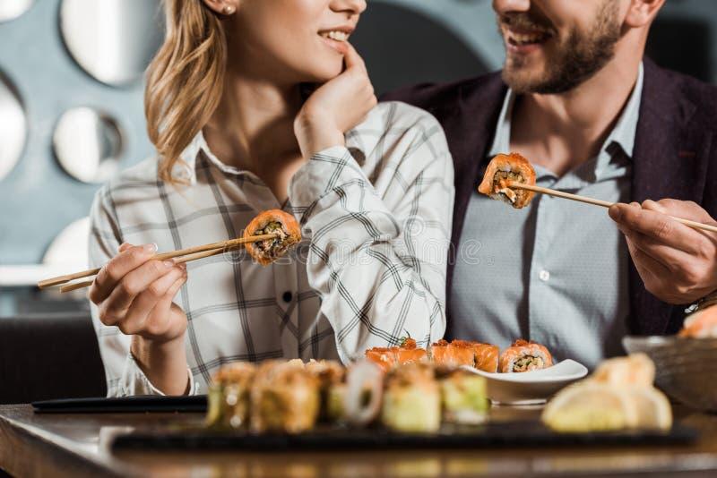 Bebouwde mening van glimlachend gelukkig paar die sushi eten stock foto's