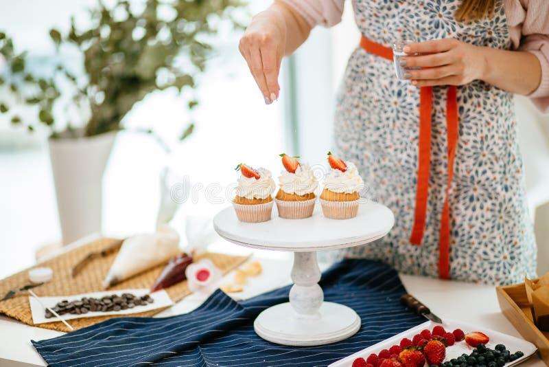 Bebouwde mening van het vrouwelijke bakker verfraaien cupcakes met bovenste laagje stock afbeeldingen